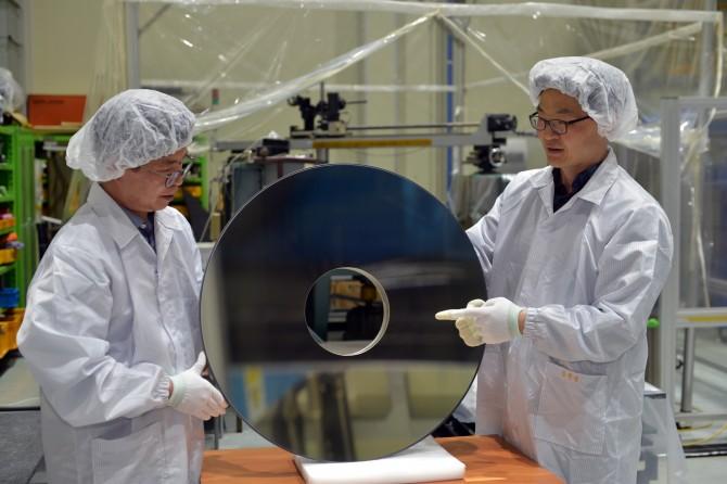 양호순 우주광학센터장(오른쪽)이 실리콘 카바이드로 만든 지름 700㎜인 비구면 반사경에 대해 설명하고 있다. - 한국표준과학연구원 제공